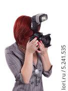 Молодая, симпатичная девушка в деловом костюме с короткой стрижкой держит в руках профессиональный фотоаппарат со вспышкой. Стоковое фото, фотограф Даниил Петров / Фотобанк Лори