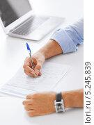 Купить «Бизнесмен в голубой сорочке работает с бумагами за столом в офисе», фото № 5245839, снято 9 июня 2013 г. (c) Syda Productions / Фотобанк Лори