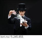 Купить «Маг-фокусник в черном цилиндре показывает карточный фокус», фото № 5245855, снято 12 сентября 2013 г. (c) Syda Productions / Фотобанк Лори
