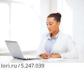Купить «Привлекательная деловая женщина работает с документами, сидя за ноутбуком», фото № 5247039, снято 1 августа 2013 г. (c) Syda Productions / Фотобанк Лори