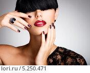 Купить «Портрет брюнетки с длинной чёлкой и красными сексуальными губами  на сером фоне», фото № 5250471, снято 23 сентября 2013 г. (c) Валуа Виталий / Фотобанк Лори