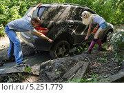 Купить «Мужчина и девушка выкапывают застрявший автомобиль», фото № 5251779, снято 24 августа 2013 г. (c) макаров виктор / Фотобанк Лори