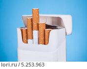 Купить «сигареты в пачке на голубом фоне», фото № 5253963, снято 9 мая 2013 г. (c) Андрей Попов / Фотобанк Лори