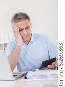 Купить «Мужчина среднего возраста размышляет над расчетами с калькулятором в руке», фото № 5269863, снято 7 апреля 2013 г. (c) Андрей Попов / Фотобанк Лори