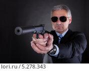 Купить «мужчина среднего возраста в темных очках целится из пистолета с глушителем», фото № 5278343, снято 7 апреля 2013 г. (c) Андрей Попов / Фотобанк Лори