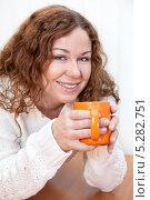 Молодая женщина с оранжевой кружкой за столом. Стоковое фото, фотограф Кекяляйнен Андрей / Фотобанк Лори