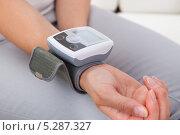 Купить «Электронный тонометр на руке молодой женщины», фото № 5287327, снято 16 июня 2013 г. (c) Андрей Попов / Фотобанк Лори