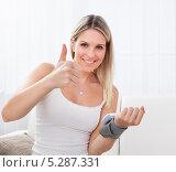 Купить «Довольная женщина с электронным тонометром на руке показывает жест одобрения», фото № 5287331, снято 16 июня 2013 г. (c) Андрей Попов / Фотобанк Лори