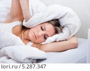 Купить «Молодая женщина лежит в кровати, закрыв уши подушкой», фото № 5287347, снято 16 июня 2013 г. (c) Андрей Попов / Фотобанк Лори