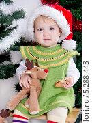 Купить «Малышка в новогодней шапочке с игрушкой и печеньем под елкой», фото № 5288443, снято 24 октября 2013 г. (c) Asja Sirova / Фотобанк Лори