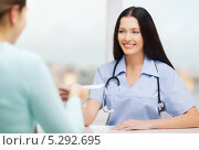 Купить «Молодой врач приветливо улыбается пациентке», фото № 5292695, снято 6 ноября 2013 г. (c) Syda Productions / Фотобанк Лори