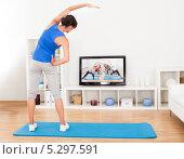 молодая женщина смотрит фитнес по телевизору и повторяет упражнение. Стоковое фото, фотограф Андрей Попов / Фотобанк Лори
