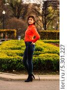 Девушка в джинсах и оранжевой куртке стоит в парке у клумбы (2013 год). Стоковое фото, фотограф Юрий Селиванов / Фотобанк Лори