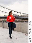 Симпатичная девушка в оранжевой куртке и джинсах гуляет по набережной (2013 год). Стоковое фото, фотограф Юрий Селиванов / Фотобанк Лори