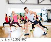Стройные девушки под руководством инструктора занимаются в фитнес-клубе. Стоковое фото, фотограф Syda Productions / Фотобанк Лори