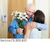 Купить «Пожилой мужчина с букетом гвоздик обнимает женщину в коридоре квартиры у входной двери», фото № 5303431, снято 20 апреля 2018 г. (c) Яков Филимонов / Фотобанк Лори