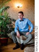 Купить «Красивый молодой мужчина сидит на диване», эксклюзивное фото № 5305127, снято 7 сентября 2013 г. (c) Игорь Низов / Фотобанк Лори