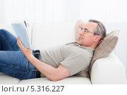 Купить «мужчина среднего возраста читает книгу, лежа на диване», фото № 5316227, снято 21 июля 2013 г. (c) Андрей Попов / Фотобанк Лори