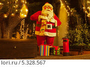 Купить «Новый Год на Мадейре. Санта-Клаус, исполняющий желания. Урна для детских записок и сундук с подарками в парке Фуншала вечером», фото № 5328567, снято 23 декабря 2011 г. (c) Виктория Катьянова / Фотобанк Лори