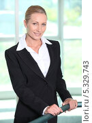 Купить «Деловая женщина стоит, держась за поручень», фото № 5329743, снято 19 мая 2010 г. (c) Phovoir Images / Фотобанк Лори