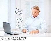Купить «Пожилой мужчина сидит за столом дома и заполняет квитанцию, сверяясь с экраном ноутбука», фото № 5352767, снято 12 октября 2013 г. (c) Syda Productions / Фотобанк Лори