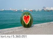 Арбуз с вырезом в форме сердца на фоне моря. Стоковое фото, фотограф Филипп Яндашевский / Фотобанк Лори