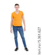 Купить «Молодой мужчина в желтой футболке и узких голубых джинсах на белом фоне», фото № 5361627, снято 8 декабря 2013 г. (c) Discovod / Фотобанк Лори