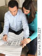 Купить «Пара рассматривает чертежи в офисе архитектора», фото № 5369227, снято 21 января 2010 г. (c) Phovoir Images / Фотобанк Лори