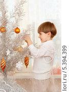 Купить «Пятилетний мальчик наряжает серебристую новогоднюю елку», фото № 5394399, снято 15 декабря 2013 г. (c) Юлия Кузнецова / Фотобанк Лори