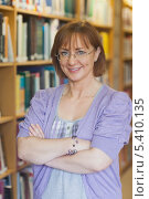 Купить «Mature female librarian posing in library with crossed arms», фото № 5410135, снято 28 августа 2013 г. (c) Wavebreak Media / Фотобанк Лори