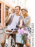 пара смотрит в экран смартфона сидя на велосипедах. Стоковое фото, фотограф Syda Productions / Фотобанк Лори