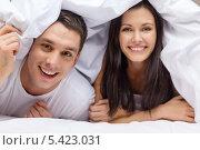 улыбающаяся пара выглядывает из-под одеяла. Стоковое фото, фотограф Syda Productions / Фотобанк Лори