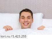 Купить «улыбающийся молодой человек выглядывает из-за одеяла», фото № 5423255, снято 23 ноября 2013 г. (c) Syda Productions / Фотобанк Лори