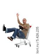Купить «Мужчина катится в магазинной тележке», фото № 5426235, снято 24 января 2011 г. (c) Phovoir Images / Фотобанк Лори