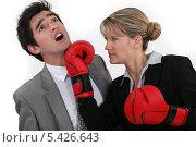 Деловая женщина в боксерских перчатках бьет конкурента в челюсть, фото № 5426643, снято 22 марта 2011 г. (c) Phovoir Images / Фотобанк Лори