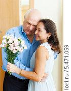 Счастливая пожилая пара стоит обнявшись. Женщина держит в руке букет цветов. Стоковое фото, фотограф Яков Филимонов / Фотобанк Лори