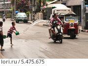 Мальчик обливает людей на мотоцикле из ведра. Редакционное фото, фотограф Гуляева Юлия / Фотобанк Лори