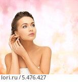 Купить «красивая брюнетка с высокой прической примеряет бриллиантовые серьги», фото № 5476427, снято 17 марта 2013 г. (c) Syda Productions / Фотобанк Лори