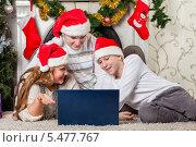 Купить «Счастливая семья в рождественских колпаках с  ноутбуком лежат около елки дома», фото № 5477767, снято 21 декабря 2011 г. (c) Мельников Дмитрий / Фотобанк Лори