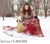 Купить «Улыбающаяся женщина чистит ковер вевником с помощью снега», фото № 5494859, снято 5 декабря 2012 г. (c) Яков Филимонов / Фотобанк Лори