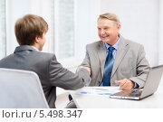 Купить «пожилой и молодой бизнесмены пожимают друг другу руки после встречи», фото № 5498347, снято 12 октября 2013 г. (c) Syda Productions / Фотобанк Лори