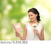Купить «красивая девушка с цветком в руке читает открытку», фото № 5510363, снято 2 марта 2013 г. (c) Syda Productions / Фотобанк Лори