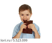 Купить «Мальчик ест плитку шоколада», фото № 5523099, снято 8 января 2014 г. (c) Александр Fanfo / Фотобанк Лори