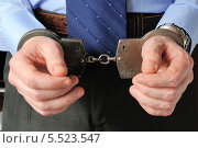 Купить «Бизнесмен держит перед собой руки в наручниках», фото № 5523547, снято 21 января 2014 г. (c) Алексей Карпов / Фотобанк Лори