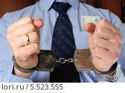 Купить «Бизнесмен держит перед собой руки в наручниках, в кармане рубашки лежат деньги», фото № 5523555, снято 21 января 2014 г. (c) Алексей Карпов / Фотобанк Лори