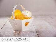 Красочные пасхальные яйца в декоративной корзинке на деревянном фоне. Стоковое фото, фотограф Елена Ефимова / Фотобанк Лори