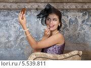 Купить «Красивая девушка с вуалью на лице красит губы помадой», фото № 5539811, снято 14 августа 2013 г. (c) Алексей Кузнецов / Фотобанк Лори