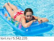 Купить «Молодая женщина плавает на матрасе в бассейне и пьет сок», фото № 5542235, снято 17 июля 2012 г. (c) Losevsky Pavel / Фотобанк Лори