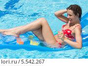 Купить «Молодая женщина плавает на матрасе в бассейне, смеется с коктейлем в руке», фото № 5542267, снято 17 июля 2012 г. (c) Losevsky Pavel / Фотобанк Лори
