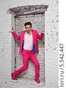 Купить «Молодой человек в розовом костюме и обуви стоит в проеме белой кирпичной стены», фото № 5542447, снято 26 ноября 2012 г. (c) Losevsky Pavel / Фотобанк Лори